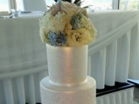 Wedding cakes 4 tier stencilled and piped overlay with pearlised luster wedding cake. Decorated with fresh flowers