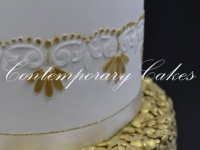 Wedding cake with gold confetti and large sugar flower